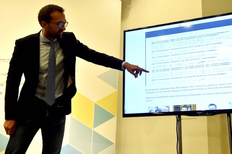The Ukrainian journalist and member of parliament Serhiy Leshchenko points to a monitor displaying a page of an illegal shadow accounting book of the party of former Ukrainian President Viktor Yanukovych, which showed alleged payments to Paul Manafort, Donald Trump's presidential campaign chairman, during a press conference in Kiev on Aug. 19, 2016. (Sergei Supinsky/AFP/Getty Images)