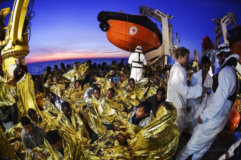 Migrants and refugees wrapped in survival foil blankets rest next to rescue members aboard the Topaz Responder ship run by Maltese NGO Moas and the Italian Red Cross after a rescue operation, early morning on November 5, 2016 off the coast of Libya. (ANDREAS SOLARO/AFP/Getty Images)