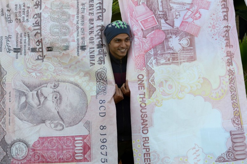A man poses with prints of the discontinued 500 and 1000 rupee notes in Mumbai on Nov. 20, 2016.  (Indranil Mukherjee/AFP/Getty Images)