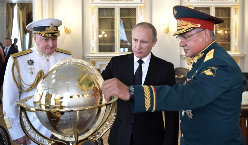 Russian President Vladimir Putin (C), Defence Minister Sergei Shoigu (R) and Commander in Chief of the Russian Navy Vladimir Korolev (L) watch a terrestrial globe while visiting Russia's Navy Headquarters during Navy Day in Saint Petersburg on July 30, 2017. (ALEXEY NIKOLSKY/AFP/Getty Images)