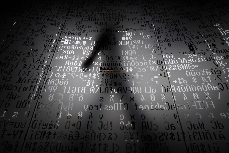 An employee walks behind a glass wall with coding symbols at the headquarters of Internet security giant Kaspersky in Moscow on October 17, 2016. (Kirill Kudryavtsev/AFP/Getty Images)