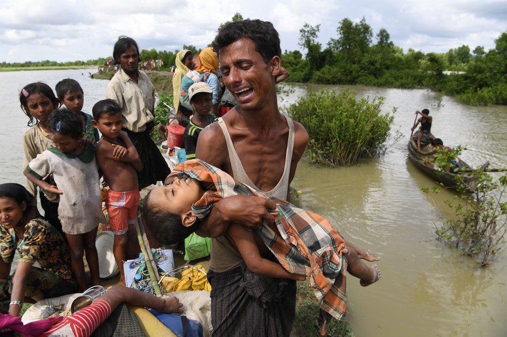 A Rohingya refugee reacts while holding his dead son after crossing the Naf river from Myanmar into Bangladesh in Whaikhyang on Oct. 9, 2017. (Indranil Mukherjee/AFP/Getty Images)