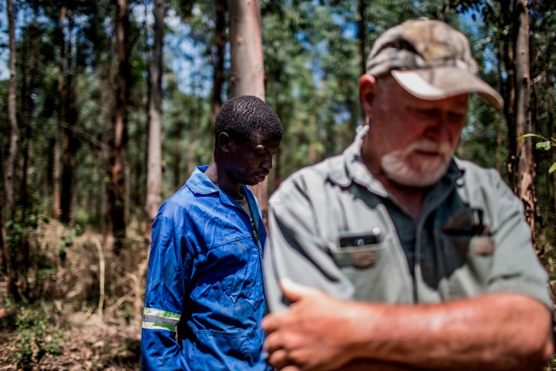 Farmworker Mogoala Justice Ratalele stands near his boss, farmer Hans Bergmann, after being held at gunpoint during a theft, in Tzaneen, South Africa, on Nov. 2, 2017. (Gulshan Khan/AFP/Getty Images)