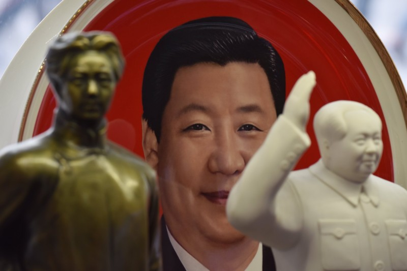 A decorative plate featuring an image of Chinese President Xi Jinping is seen behind statues of late communist leader Mao Zedong at a souvenir store next to Tiananmen Square in Beijing on February 27. (Greg Baker/AFP/Getty Images)