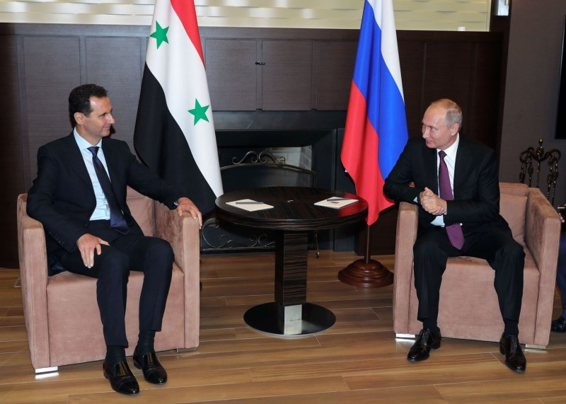 Russian President Vladimir Putin speaks with his Syrian counterpart, Bashar al-Assad, during their meeting in Sochi, Russia, on May 17. (Mikhail Klimentyev/AFP/Getty Images)
