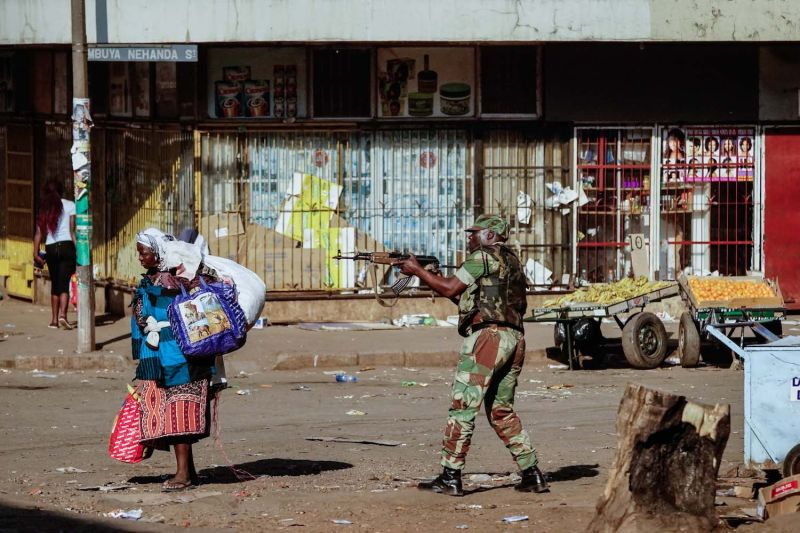 A vendor scurries for cover as soldiers disperse demonstrators in Harare on Aug. 1. Protests erupted in the Zimbabwean capital over alleged electoral fraud. (Zinyange Auntony/AFP/Getty Images)