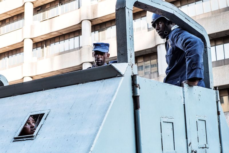 Zimbabwean police officials look at detained civilians as they stand in an armored vehicle outside MDC party headquarters in Harare on August 2, 2018.