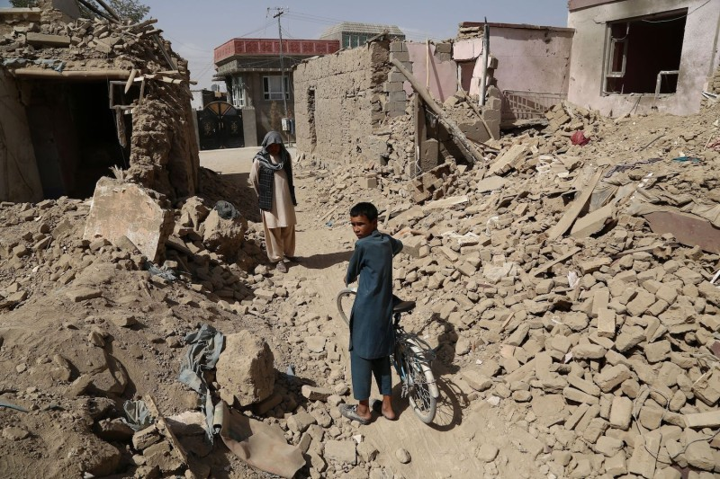 People walk near destroyed houses after a Taliban attack in Ghazni, Afghanistan on Aug. 16. (Zakeria Hashimi/AFP/Getty Images)