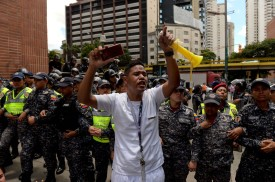 A health worker shouts slogans demanding fair and higher wages during a protest of the lack of medical supplies and poor conditions in hospitals, in front of a line of police  in Caracas on Aug. 16. (Federico Parra/AFP/Getty Images)