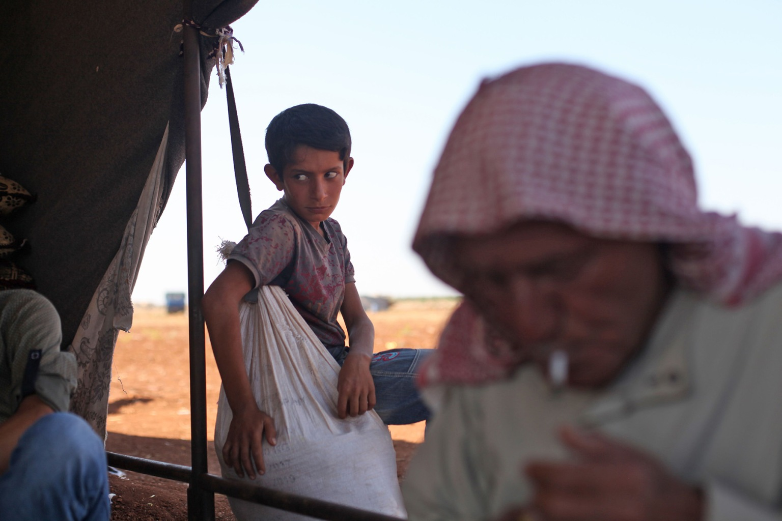 An elderly Syrian lights a cigarette as a child stands behind him outside a tent at a camp for displaced civilians fleeing from advancing Syrian government forces near the village of Sarman in the rebel-held northwestern Idlib province on Sept. 5. AMER ALHAMWE/AFP/Getty Images