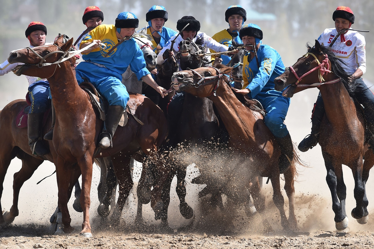 Russian and Kazakh riders play the traditional Central Asian sport buzkashi during the World Nomad Games in Cholpon-Ata, eastern Kirghizstan, on Sept. 5. Players compete for possession of a headless animal carcass and try to get it in a goal. VYACHESLAV OSELEDKO/AFP/Getty Images