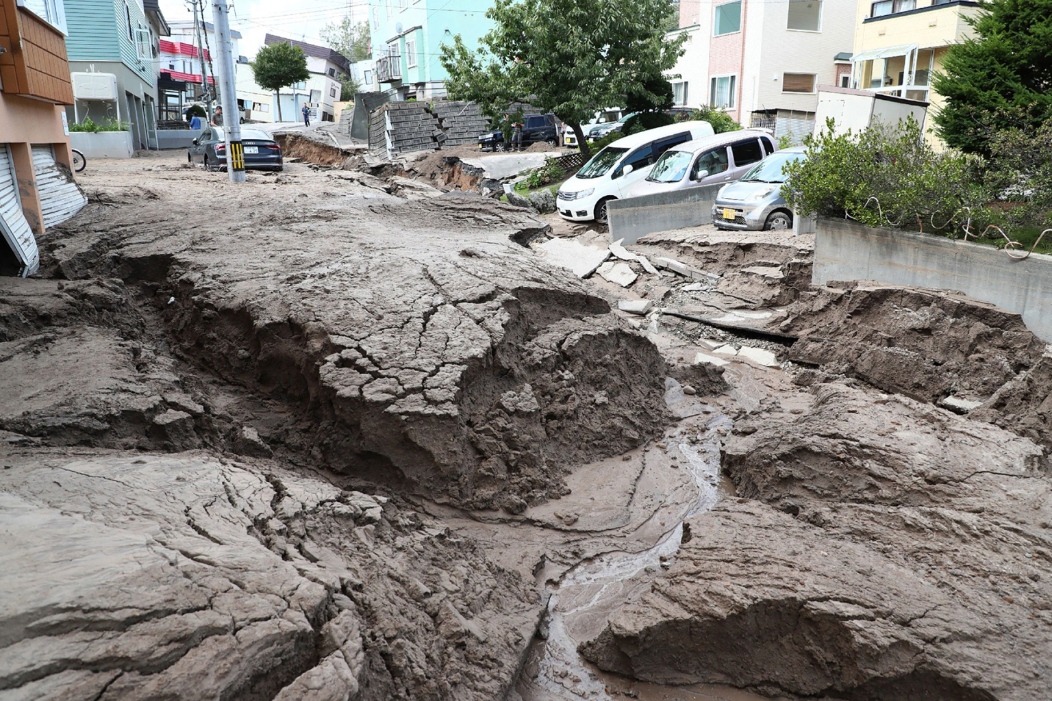 Cars tilt toward an earthquake-damaged road in Sapporo, Hokkaido prefecture, Japan on Sept. 6. A powerful 6.7-magnitude quake rocked the northern Japanese island, triggering landslides, collapsing buildings, and killing at least 18 people with dozens of others missing. JIJI PRESS/AFP/Getty Images