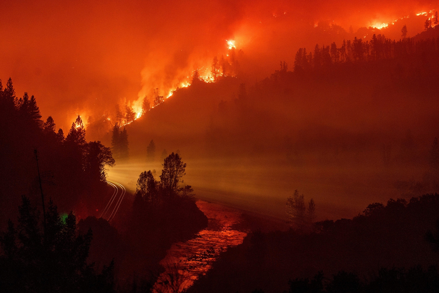 Light from a train is seen as it rounds a bend near the Sacramento River as flames from the Delta Fire fill a valley in Delta, California, on Sept. 6. JOSH EDELSON/AFP/Getty Images