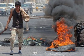 A Yemeni man walks past burning tires in Aden on Sept. 6. (Saleh al-Obeidi/AFP/Getty Images)