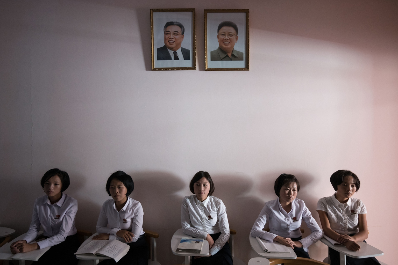 Students sit beneath the portraits of late North Korean leaders Kim Il Sung and Kim Jong Il during a tour for visiting foreign media at a teacher training college in Pyongyang on Sept. 7. ED JONES/AFP/Getty Images