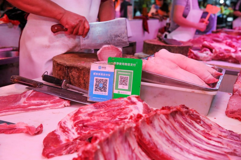 Alipay and WeChat QR codes for online payment are displayed at a meat stall at a market in Nantong in China's eastern Jiangsu province. Sept. 10.(STR/AFP/Getty Images)