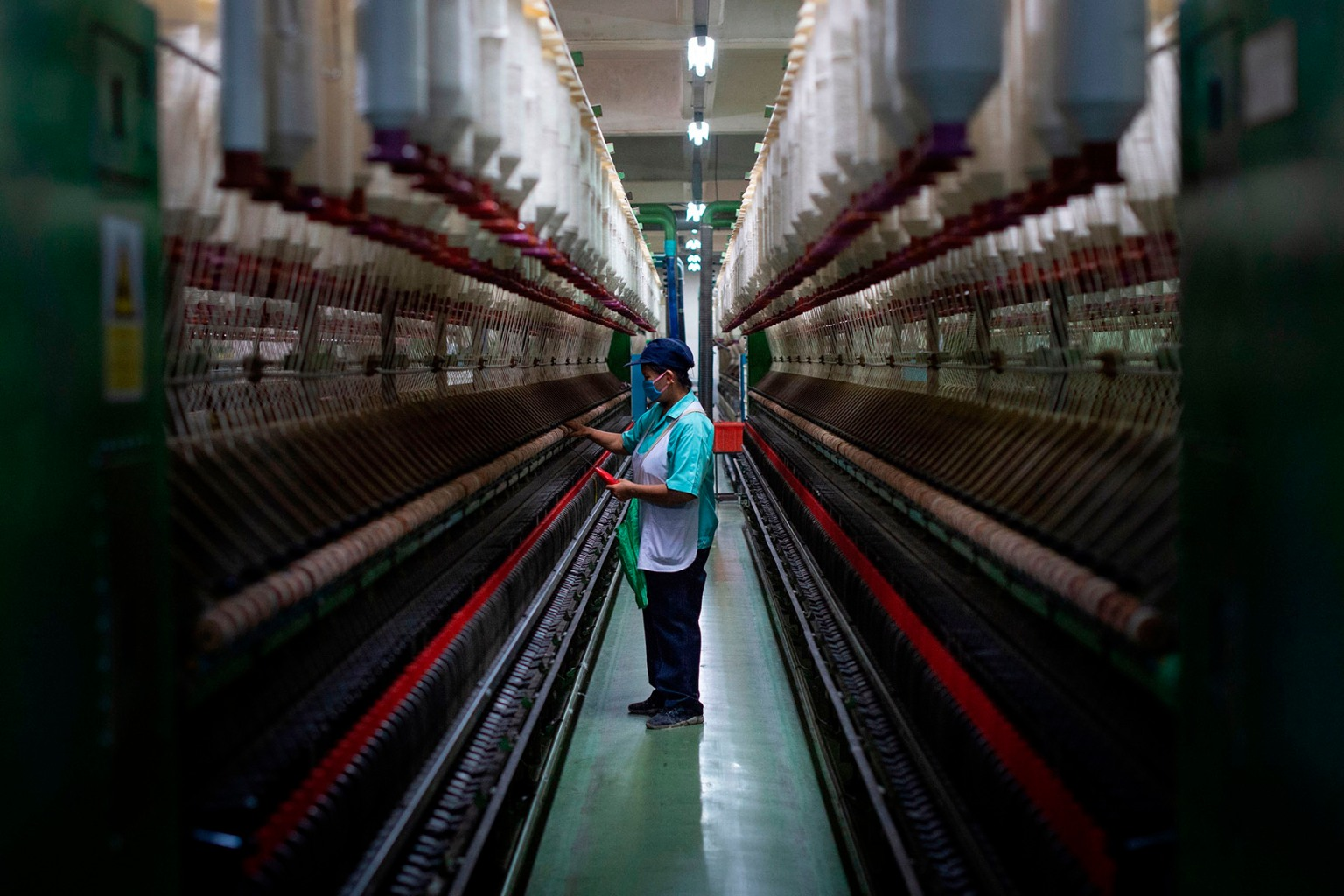 A worker monitors a spinning machine at a textile factory in Pathum Thani, Thailand, on Sept. 23. (LILLIAN SUWANRUMPHA/AFP/Getty Images)