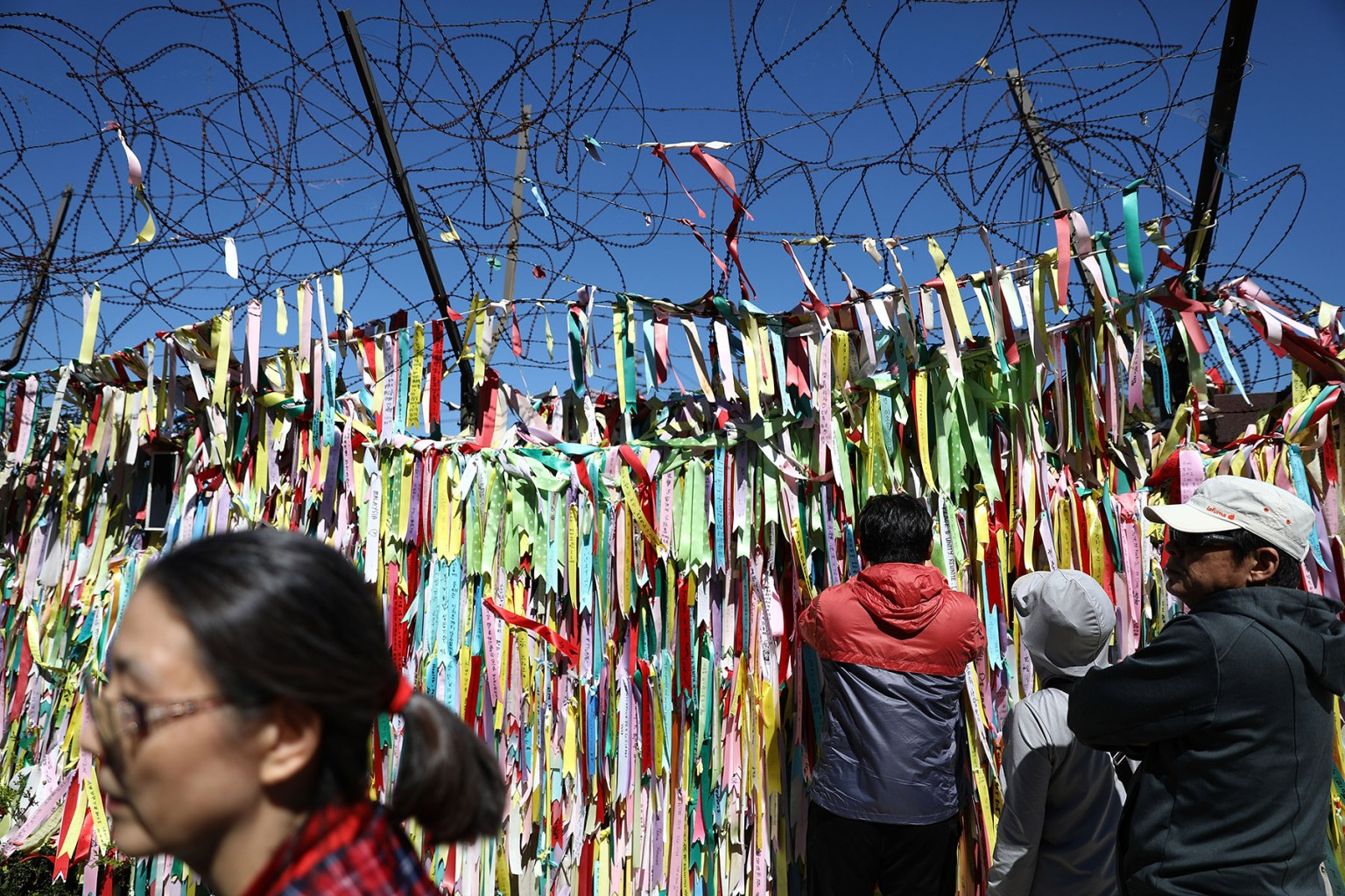 PAJU, SOUTH KOREA - SEPTEMBER 24:  South Koreans hang ribbons wishing for reunification of the two Koreas on the wire fence at the Imjingak Pavilion, near the demilitarized zone (DMZ) separating South and North Korea during Chuseok, the Korean Thanksgiving Day, on Sept. 24. Chung Sung-Jun/Getty Images