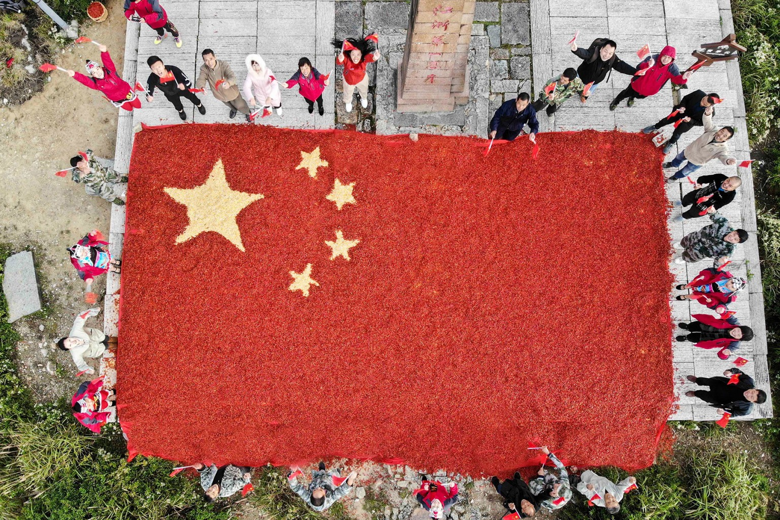 Farmers pose with a Chinese national flag made from chilli peppers and corn on Longquan mountain in Lishui in China's eastern Zhejiang province on Sept. 26. Farmers made the flag to mark the upcoming National Day. -/AFP/Getty Images