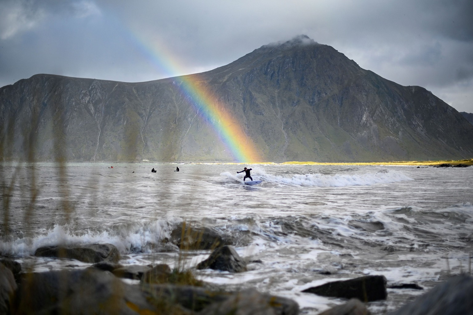 A surfer rides a wave under a rainbow during a free surf session in Flakstad, northern Norway, on Sept. 26, . The Lofoten Masters, the most northern surfing contest, is held within the Arctic circle. OLIVIER MORIN/AFP/Getty Images