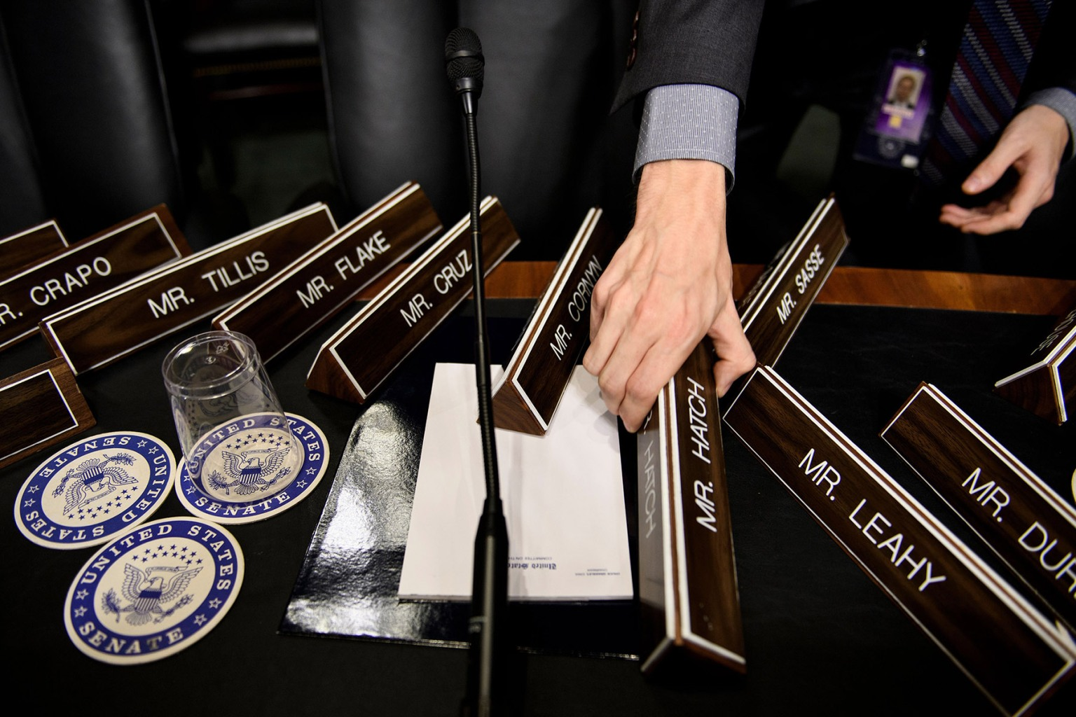 A staff member places nameplates in the committee's room on Capitol Hill ahead of the hearing on Supreme Court nominee Brett Kavanaugh on Sept. 26. BRENDAN SMIALOWSKI/AFP/Getty Images