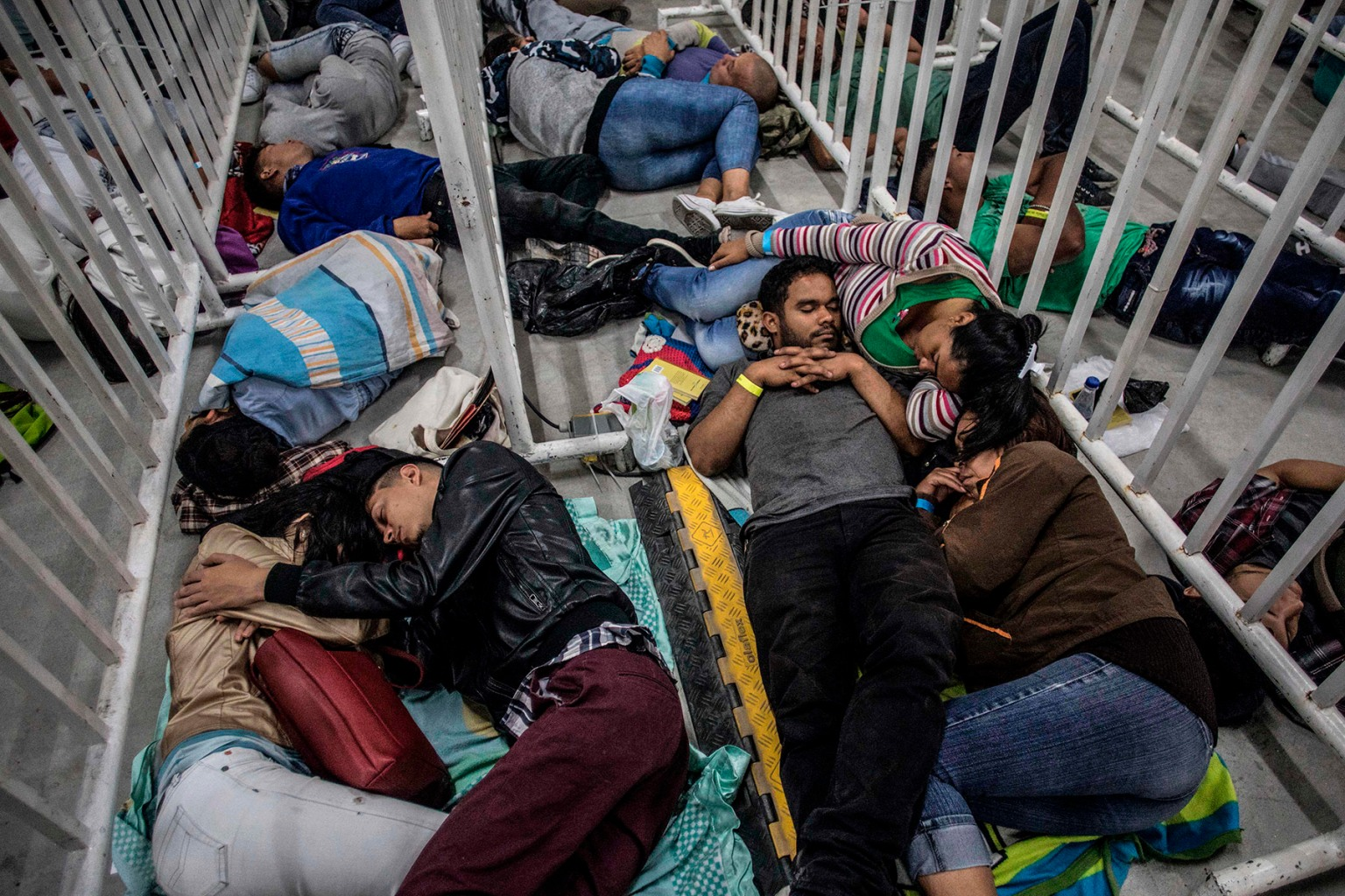 Venezuelans migrants sleep as they wait to attend the second Job Fair for Venezuelans in Colombia, on Sept. 27. JOAQUIN SARMIENTO/AFP/Getty Images