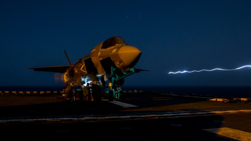 U.S. marines load ordnance into an F-35B Lightning II aboard the Wasp-class amphibious assault ship USS Essex in preparation for the F-35B's first combat strike on Sept. 27. (Photo by Cpl. A. J. Van Fredenberg/U.S. Marine Corps via Getty Images)