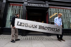 Two employees of Christie's auction house maneuver the Lehman Brothers corporate logo before placing it in an auction on Sept. 24, 2010. (Oli Scarff/Getty Images)