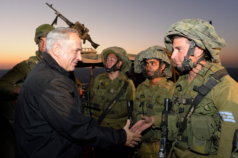 Prime Minister Benjamin Netanyahu (L) shakes hands with soldiers October 15, 2013 in the Israeli-occupied territory of Golan Heights. (Kobi Gideon/GPO via Getty Images)