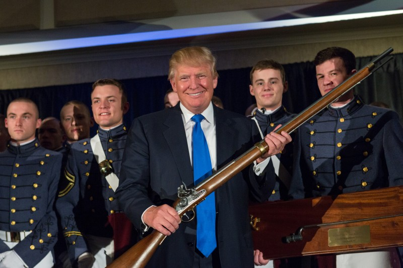 Donald Trump holds up a replica flintlock rifle awarded him by cadets during the Republican Society Patriot Dinner at the Citadel Military College on February 22, 2015 in Charleston, South Carolina. (Richard Ellis/Getty Images)