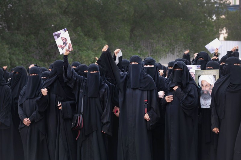 Saudi Shiite women hold placards with portraits of prominent Shiite Muslim cleric Nimr al-Nimr on January 2, 2016. (STR/AFP/Getty Images)