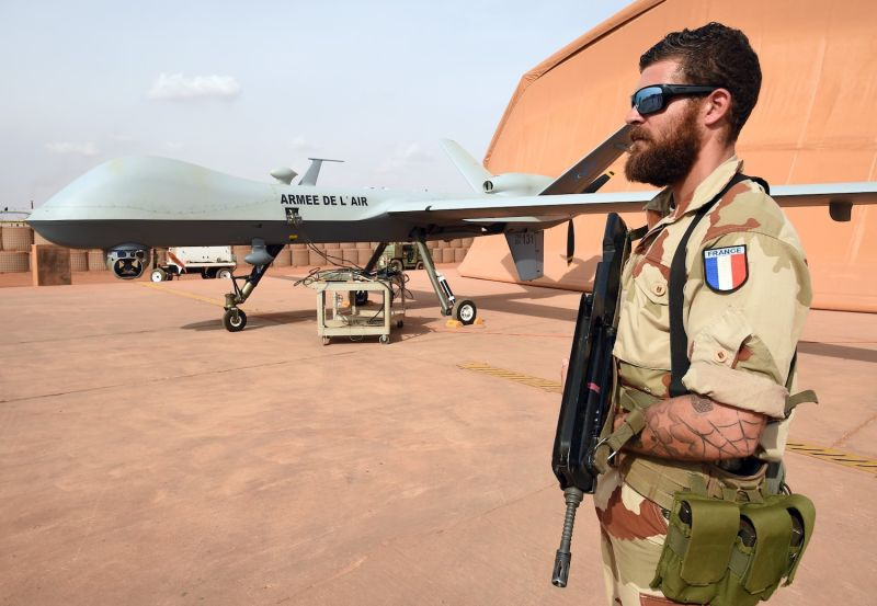 A French soldier involved in the regional anti-insurgent Operation Barkhane stands guard next to a Reaper drone at the French military air base in Niamey, Niger, on March 14, 2016. (Pascal Guyot/AFP/Getty Images)