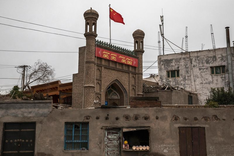 A Chinese flag flies over a local mosque closed by authorities as an ethnic Uighur woman sells bread at her bakery in Kashgar, Xinjiang province, China, on June 28, 2017. (Kevin Frayer/Getty Images)