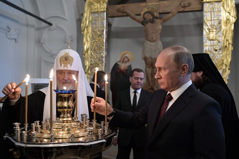 Russian President Vladimir Putin (R), accompanied by Patriarch of Russia Kirill and Prime Minister Dmitry Medvedev, places a candle as he visits the New Jerusalem Orthodox Monastery outside the town of Istra, some 70 km outside Moscow, on November 15, 2017. (ALEXEY NIKOLSKY/AFP/Getty Images)