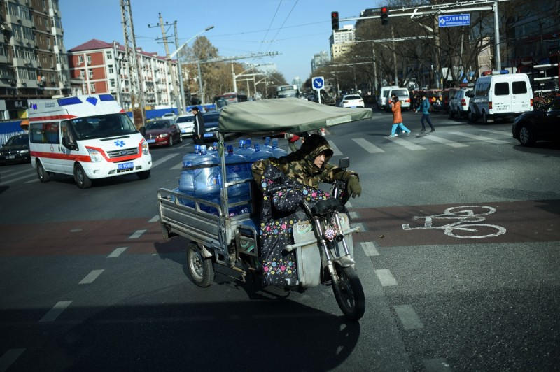 A courier riding an electric tricycle with barrels of water crosses a street in Beijing on January 22, 2018.     (WANG ZHAO/AFP/Getty Images)
