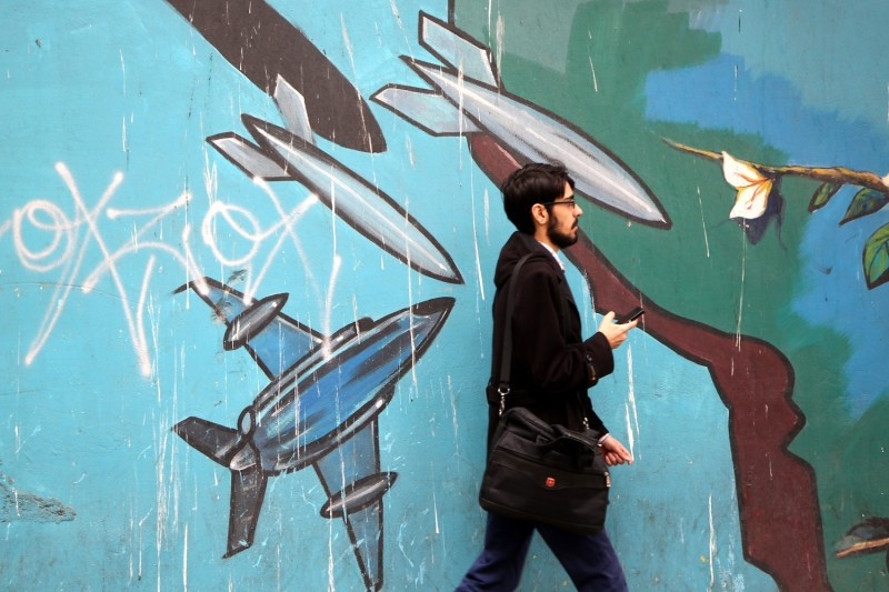 A man passes a mural painted on the wall of the former U.S. Embassy in Tehran, Iran, on May 9, 2018. (Fatemeh Bahrami/Anadolu Agency/Getty Images)