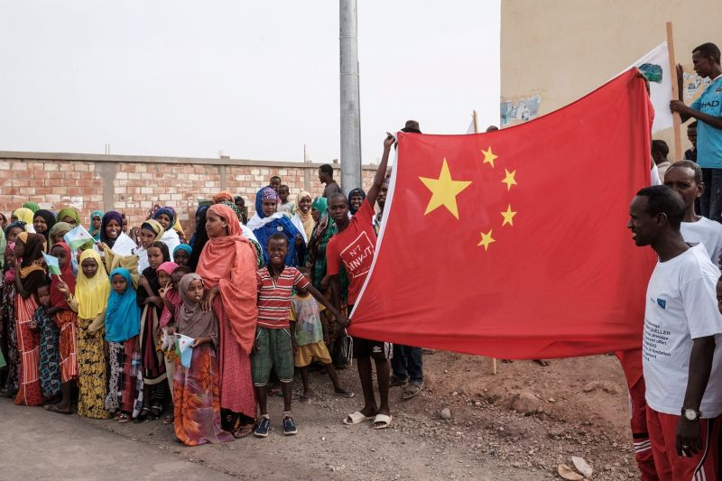 Djiboutians hold a Chinese flag before the launch ceremony of a Chinese-funded construction project in Djibouti, on July 4, 2018. (YASUYOSHI CHIBA/AFP/Getty Images)