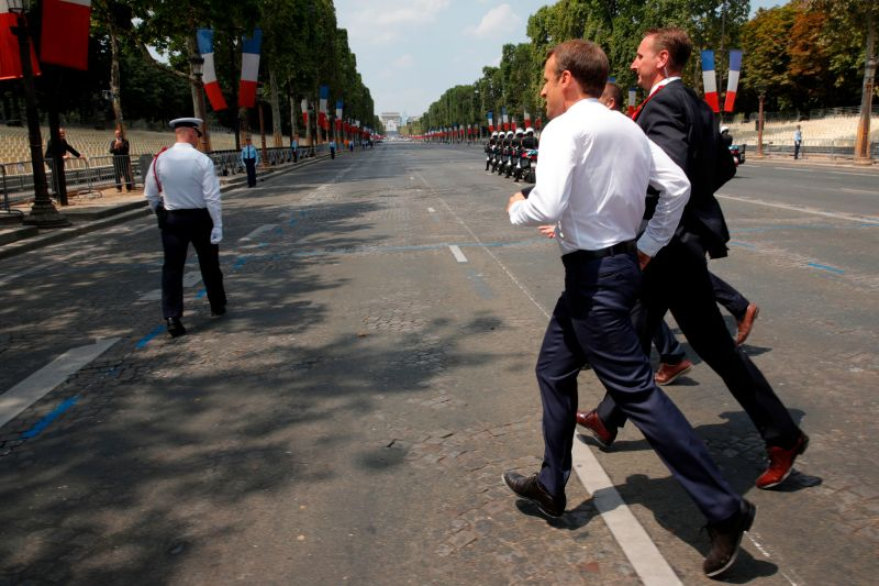 French President Emmanuel Macron runs to greet people, after the annual Bastille Day military parade on the Champs-Elysees avenue in Paris on July 14, 2018. (PHILIPPE WOJAZER/AFP/Getty Images)