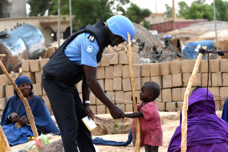 A United Nations  peacekeeper speaks to a child while on patrol through the streets Gao, Mali on August 3, 2018.