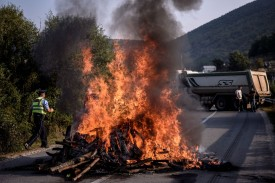 A Kosovar police officer walks past burning logs as Kosovo Albanians gather around a barricade blocking access to a village due to be visited by the Serbian President Aleksandar Vucic, on the main road between Mitrovica, in the north of Kosovo, and the village of Banje, a Serbian enclave on Sept. 9.