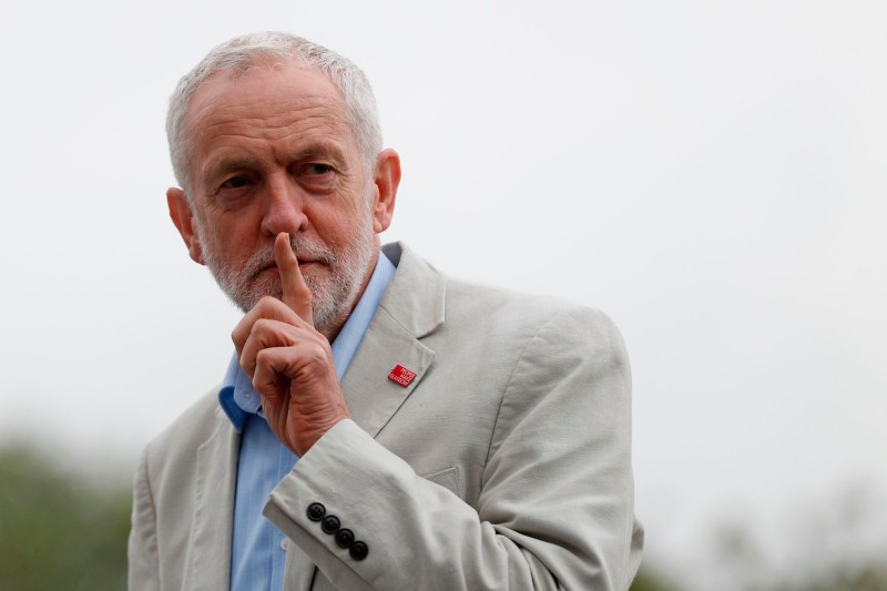 Britain's Labour Party leader, Jeremy Corbyn, gestures to the crowd not to cheer him before he speaks during a rally in central London on May 12, 2018.