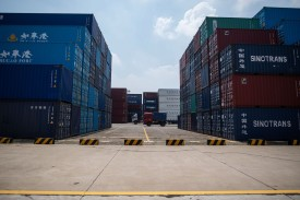 A truck transports a shipping container at a port in Zhangjiagang, China, on Aug. 7. (Johannes Eisele/AFP/Getty Images)