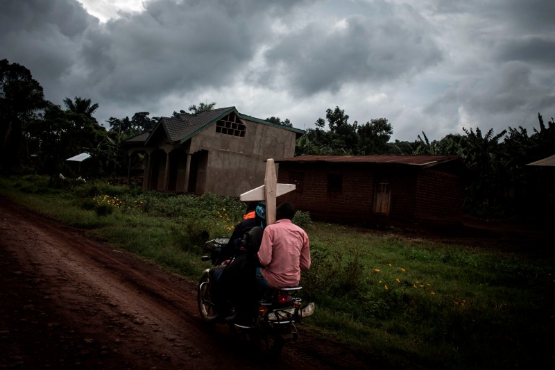 Three Congolese ride a motorbike and carry a cross for a grave in Mangina, North Kivu province, Democratic Republic of the Congo, on Aug. 23. (John Wessels/AFP/Getty Images)