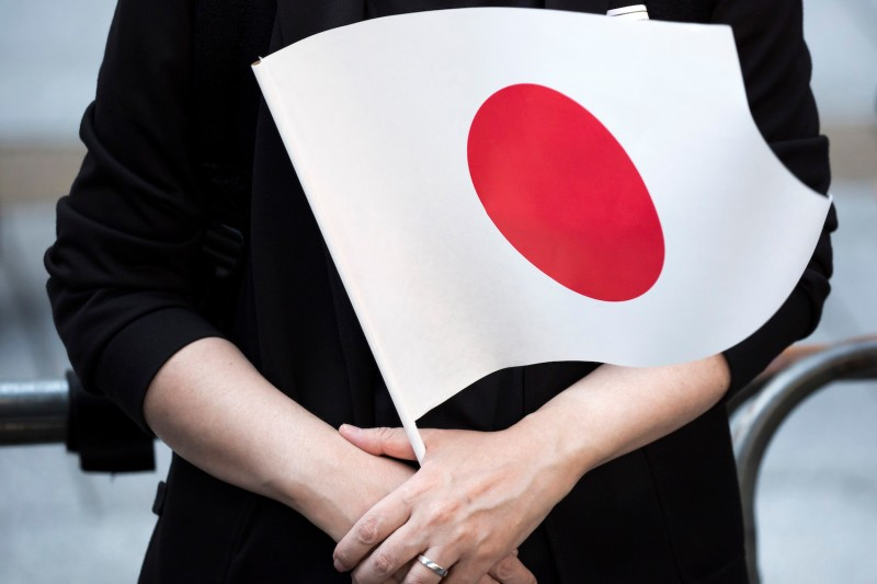 A woman holds a Japanese flag as she listens to Prime Minister Shinzo Abe speaking during a rally in Tokyo on Sept. 19. (Tomohiro Ohsumi/Getty Images)