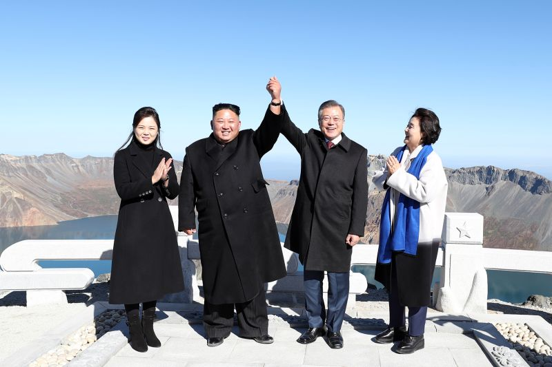 North Korean leader Kim Jong Un and South Korean President Moon Jae-in, shown with their wives Ri Sol Ju, left, and Kim Jung-sook, join hands on the top of Mount Paektu in North Korea on Sept. 20 during the recent Inter-Korean summit talks. (Pyeongyang Press Corps/Pool/Getty Images)