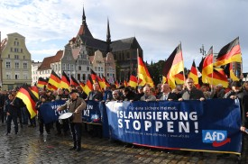"""People carry German flags and a banner which reads """"Stop Islamization"""" during a march organized by the far-right AfD party in Rostock,  Germany on September 22, 2018."""