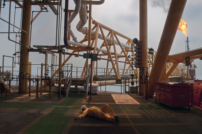 An oil worker lies on a deck during a fire drill aboard the Pemex Ku-S oil processing center in the Gulf of Mexico on Aug. 5, 2010. (Alfredo Estrella/AFP/Getty Images)