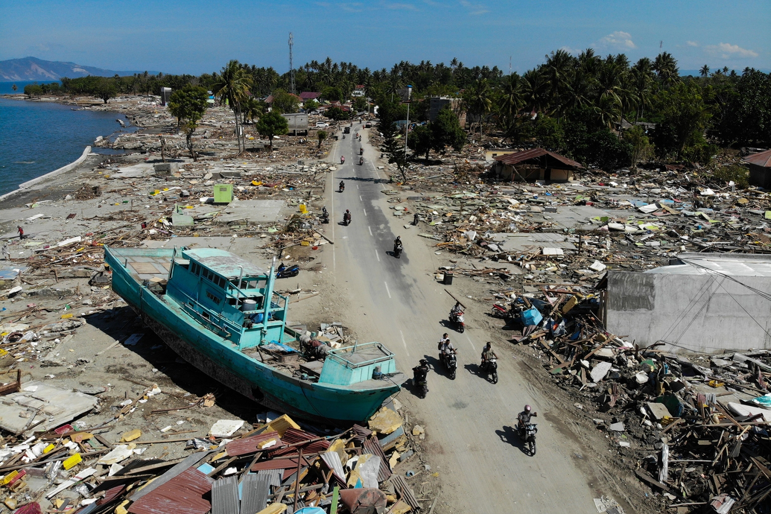People drive past a washed-up boat and collapsed buildings in Palu, Indonesia, on Oct. 1 after an earthquake and tsunami hit the area on Sept. 28. (Jewel Samad/AFP/Getty Images)