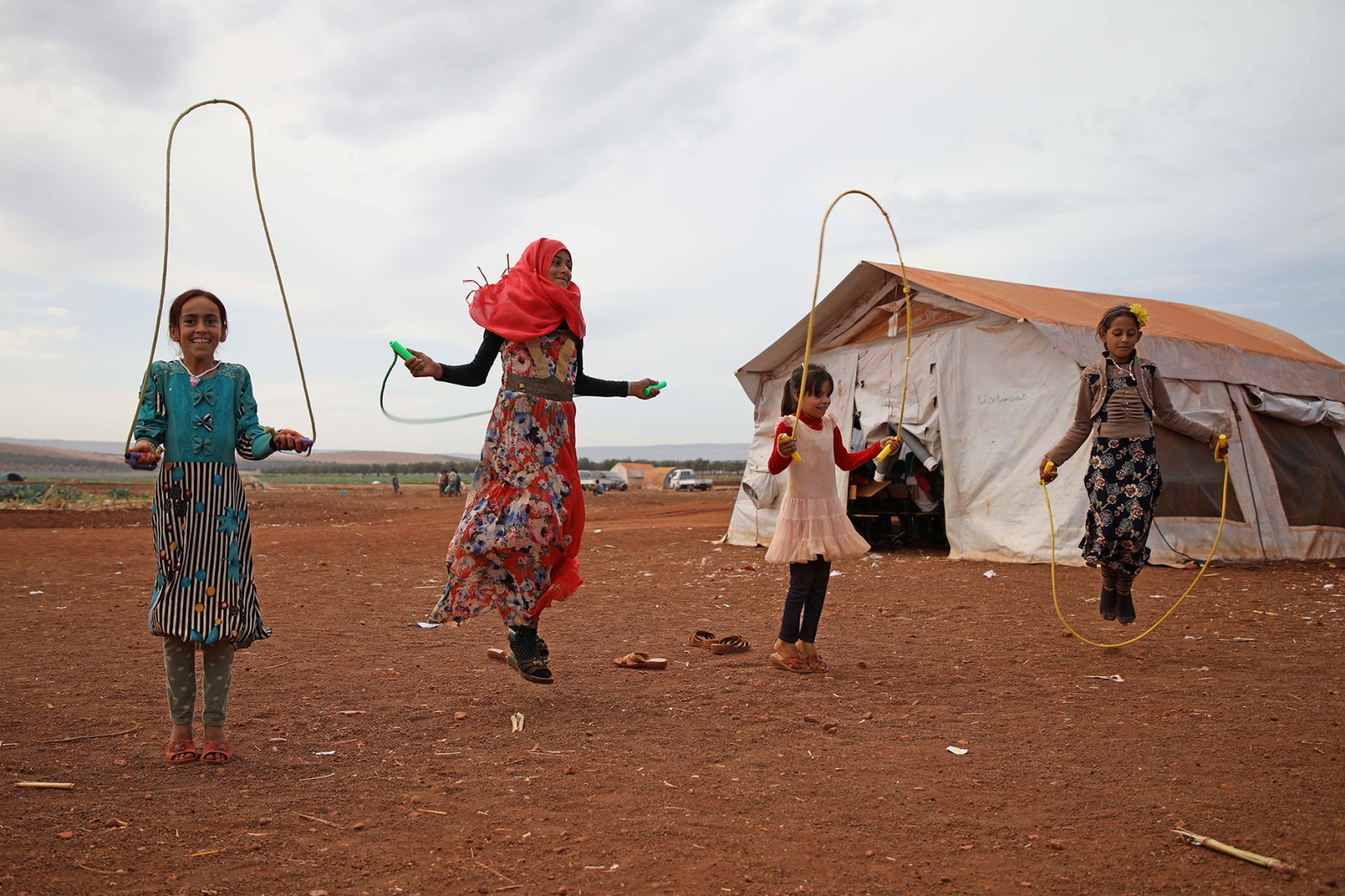 "Syrian children who fled with their families from the northern countryside of Hama jump rope at the makeshift school of Zuhur al-Mustaqbal (""Flowers of the Future"" in in Arabic) in al-Jeneinah camp in Syria's mostly rebel-held northern Idlib province on Oct. 1. AAREF WATAD/AFP/Getty Images"