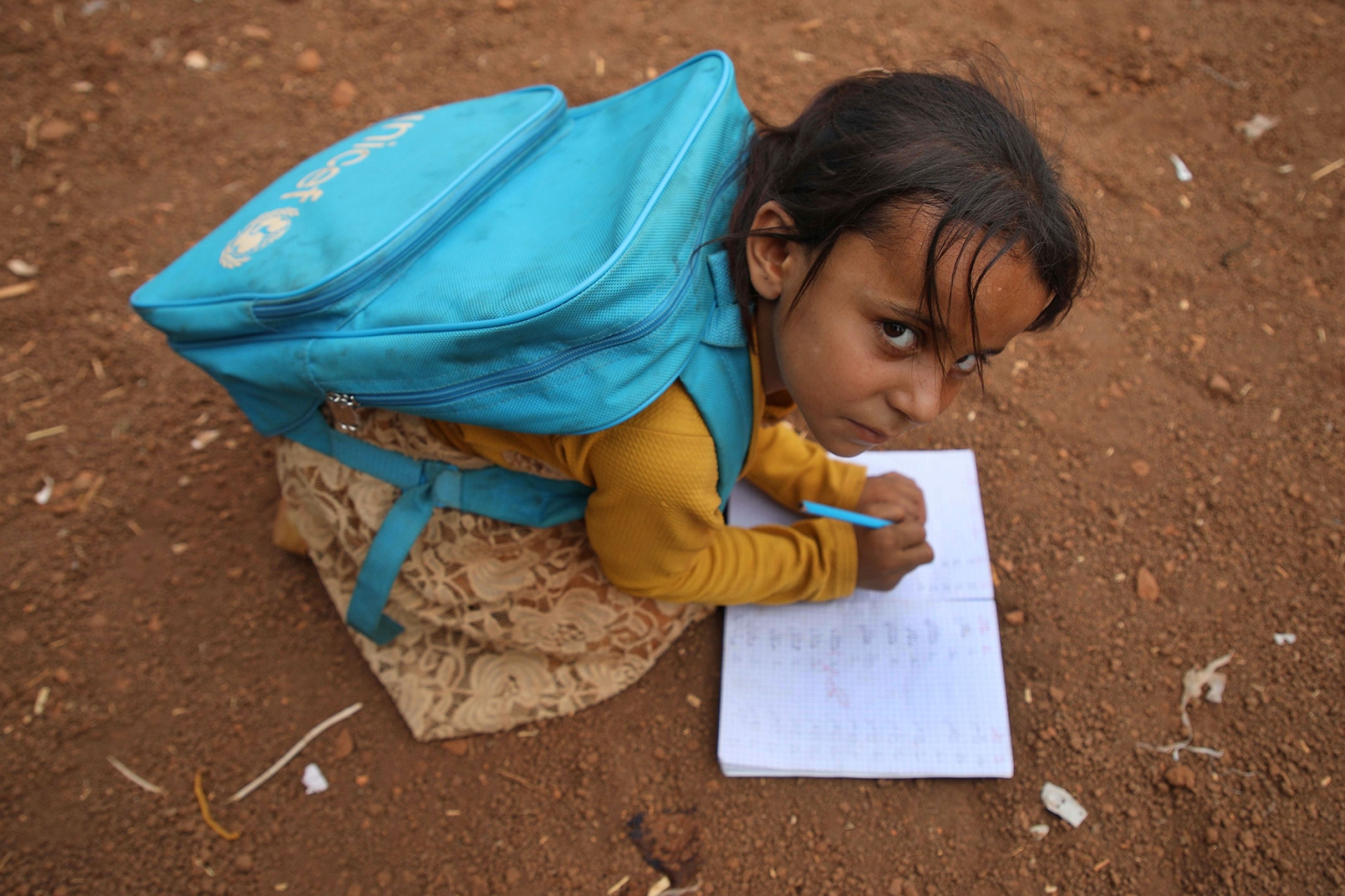 A Syrian child who fled with her family from Hama writes in a notebook in the yard of the Zuhur al-Mustaqbal school at the al-Jeneinah camp in Idlib on Oct. 1. AAREF WATAD/AFP/Getty Images